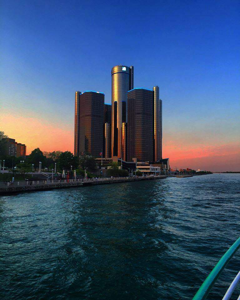 Detroit building on the horizon of the Detroit River during sunset.