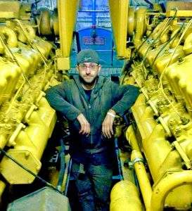 Boat engineer leaning on yellow engines