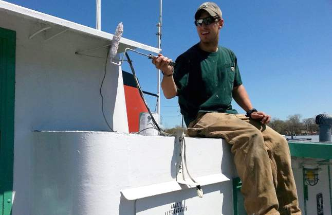 Crewman painting boat