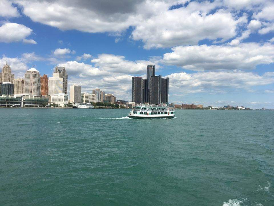 A Diamond Jack Riverboat in the Detroit River with the Detroit skyline behind